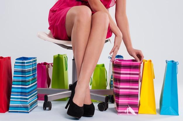 Женщина сидит на стуле рядом с хозяйственными сумками