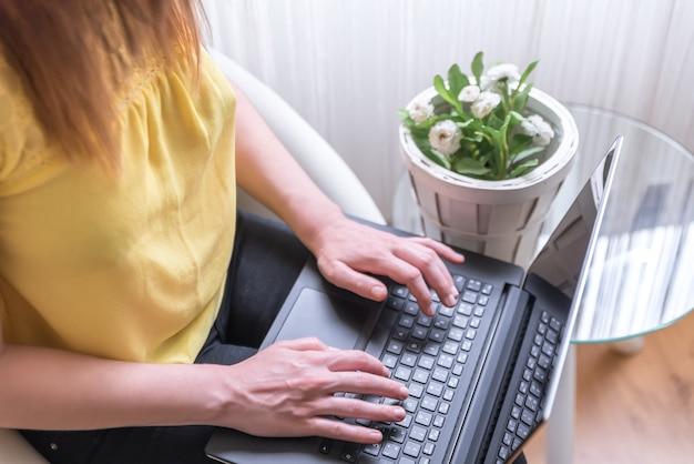 膝の上でラップトップを使用して椅子に座っている女性