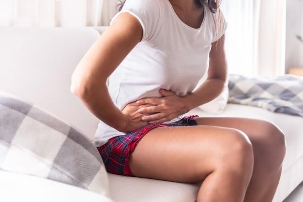 Женщина сидит на диване у себя дома, держа аппендикс от боли в животе.