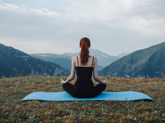 Женщина, сидящая на циновке медитации йоги асаны природы свежем воздухе. фото высокого качества