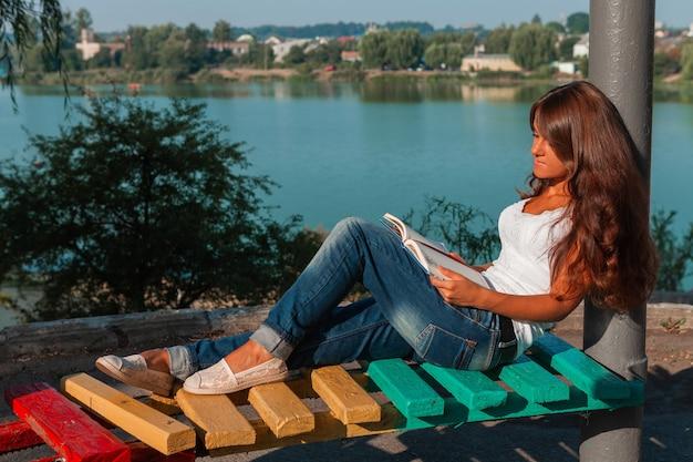 公園のベンチに座って本を読んでいる女性。屋外で読む女性