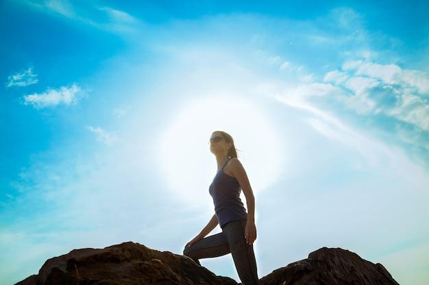 崖の頂上に座って、登った後に休んでいる女性。スポーツウェアの女の子、健康的なライフスタイル。