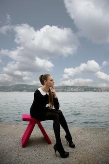 Женщина сидит на розовом кресле на пляже