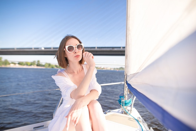 セーリングヨットの上に座って、川と橋の背景でカメラ目線の女性