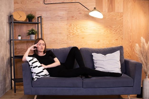 テレビを見ている居心地の良い部屋のソファに座って、画面に表示されているものに腹を立てている女性