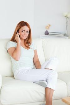 携帯電話でソファに座っている女性