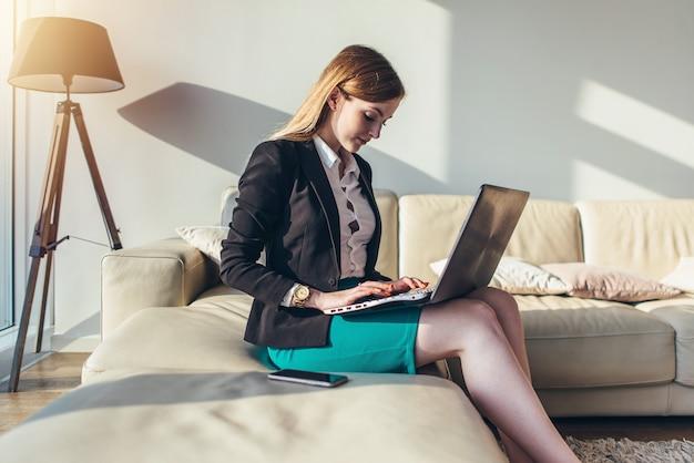 Женщина, сидящая на диване с ноутбуком на коленях, набирает текст на клавиатуре у себя дома.
