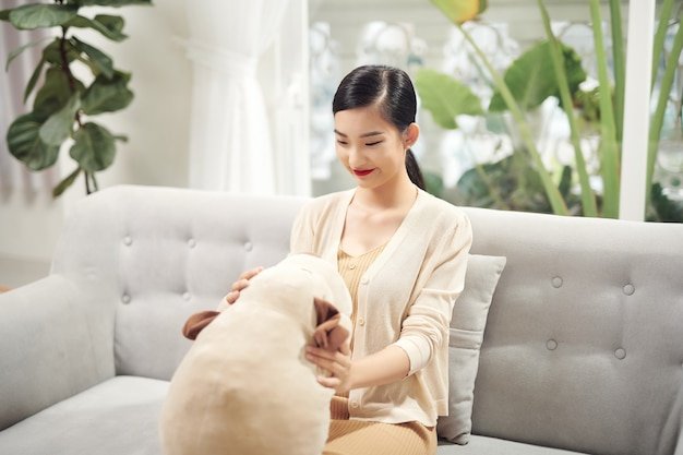 おもちゃの犬と一緒にソファに座っている女性