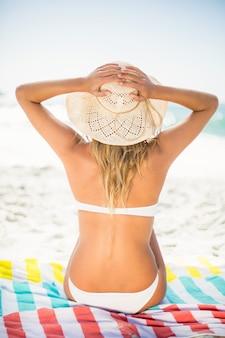 Женщина, сидящая на полотенце на пляже