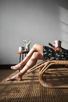 Женщина, сидящая на плетеном сиденье с чашкой чая