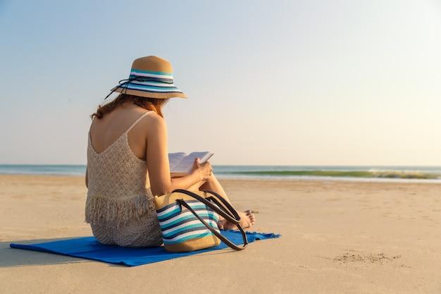 Женщина сидит на пляже и читает книгу