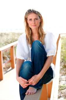 Woman sitting on beach path railing smiling