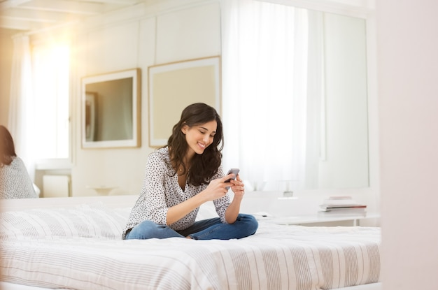 スマートフォンでテキストメッセージを読んでベッドに座っている女性