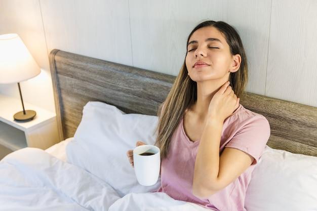 Женщина сидит на кровати с закрытыми глазами, держа чашку кофе или чая