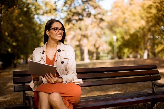 Женщина сидит на скамейке в парке в осеннюю погоду с помощью планшетного пк и проверяет социальные сети.