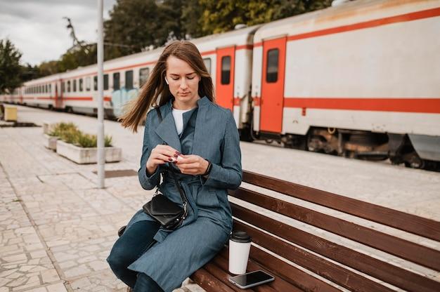 Женщина сидит на скамейке рядом с ее кофе
