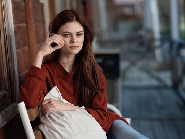 自宅のテラスのベンチに座っている女性