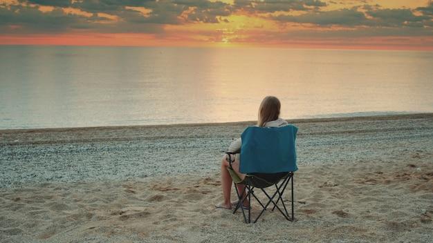 キャンプチェアに座ってコーヒーを飲む女性。リラックスして自然を楽しんでください。海の日の出を眺める。