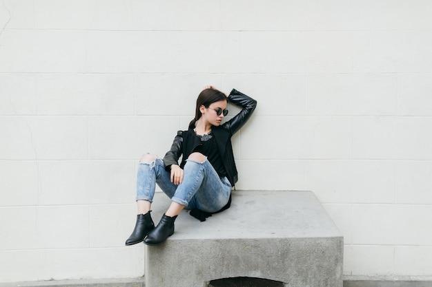 Женщина, сидящая на цементном кубе