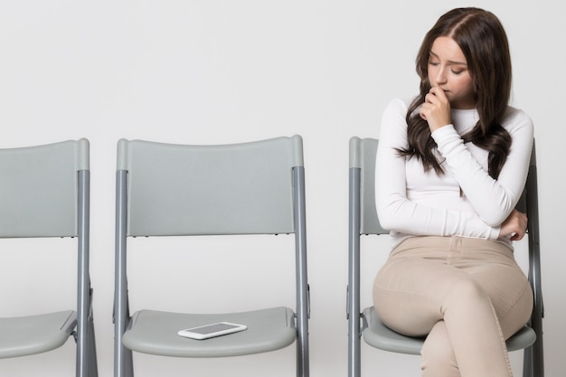 Женщина сидит на стуле и смотрит на смартфон, ожидая телефонного звонка или текстового сообщения