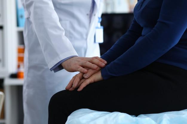 Женщина сидит в клинике, врач успокаивает пациента