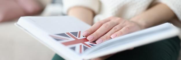 Женщина сидит на диване и держит блокнот с флагом великобритании крупным планом, изучает английский язык