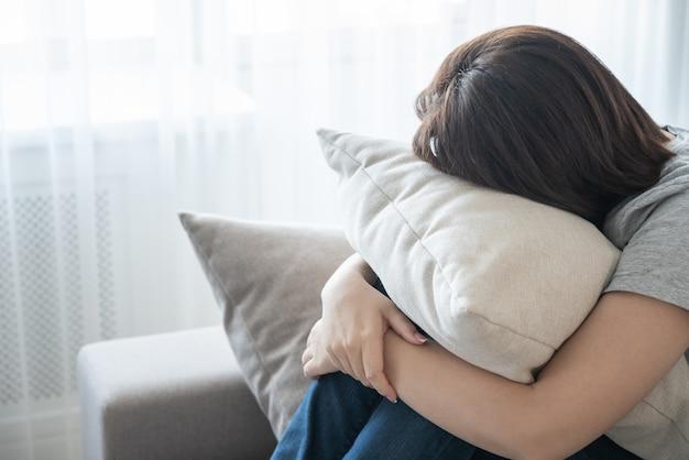 ソファに座って、枕、孤独、悲しみの概念を抱き締める女性