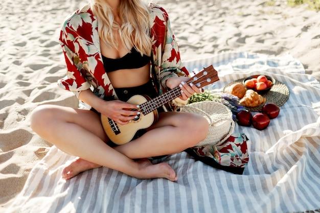 夕焼けの柔らかな色でビーチのカバーに座って、ウクレレギターを弾く女性。プレートに新鮮なフルーツ、クロワッサン、ピーチ。