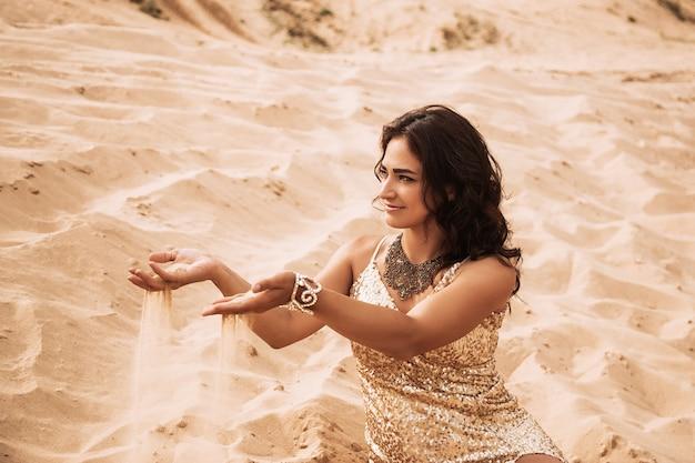 Женщина сидит на песке пустыни и держит в руке раскидистый песок.