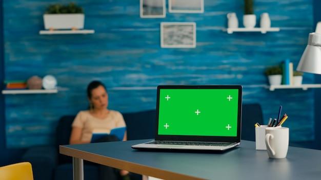 モックアップグリーンスクリーンクロマキーと分離されたラップトップコンピューターを使用してビジネス商取引に取り組んでいる机のテーブルに座っている女性。ホームオフィスのスタジオでpcに入力する白人女性