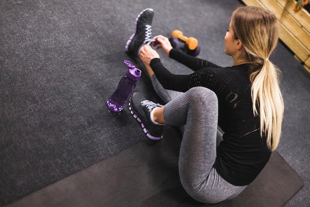 Женщина, сидя на тренировочный мат, связывая шнурки