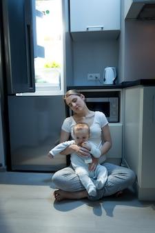 夜に台所の床に座って、哺乳瓶から赤ちゃんを養う女性