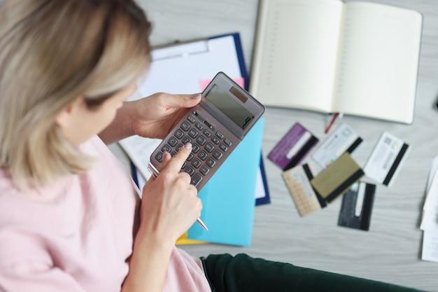 散らばった銀行カードの近くの床に座って、電卓を頼りに女性