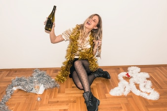 Woman sitting on floor with champagne bottle