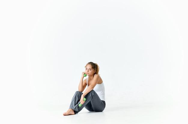 ダンベルで床に座っている女性は、フィットネスライトの背景を行使します。