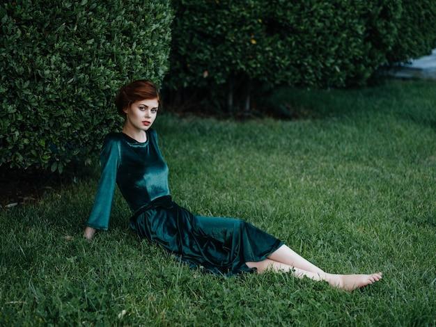 庭の自然の夏のカーニバルで緑の芝生に座っている女性