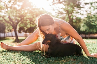 Woman sitting on green grass kissing her dog at park