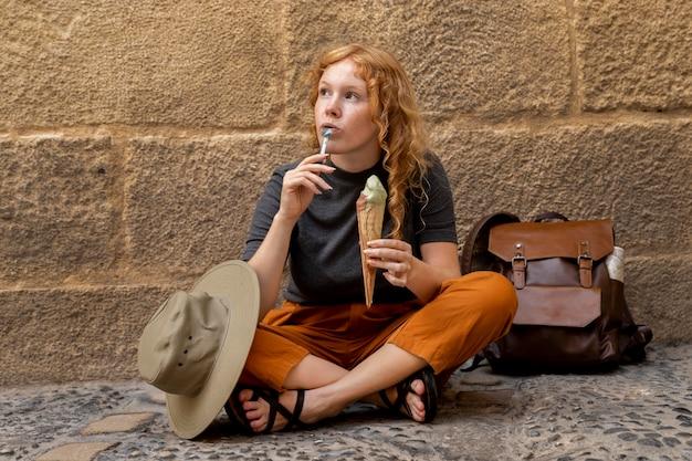 Женщина сидит на земле и ест рожок мороженого