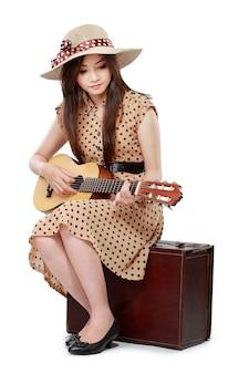 Женщина сидит на чемодане во время игры на гитаре