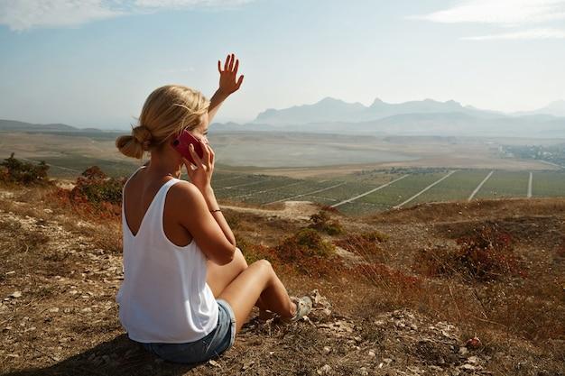 丘の上に座って電話で話している女性