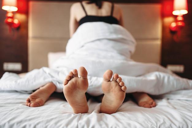 男は後ろ姿で座っている女性。ベッドでの親密なゲーム、下着での情熱的な愛好家。寝室で抱き締めるセクシーな愛のカップル