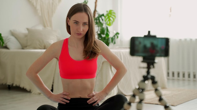 Женщина сидит на коврике и записывает видео со смартфона на штативе, занимается йогой дома и растягивает спортивное тело