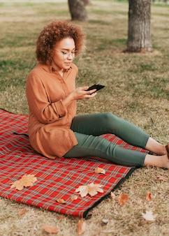 Женщина сидит на одеяле для пикника, проверяя свой телефон