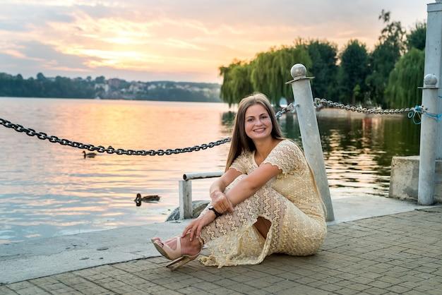 물과 일몰에 대 한 부두에 앉아 여자