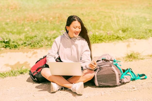 Женщина сидит на дороге, улыбаясь и держа мобильный телефон среди рюкзаков