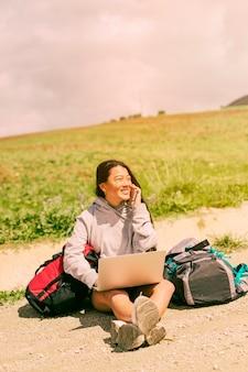Женщина сидит на дороге, улыбается и разговаривает по мобильному телефону среди рюкзаков