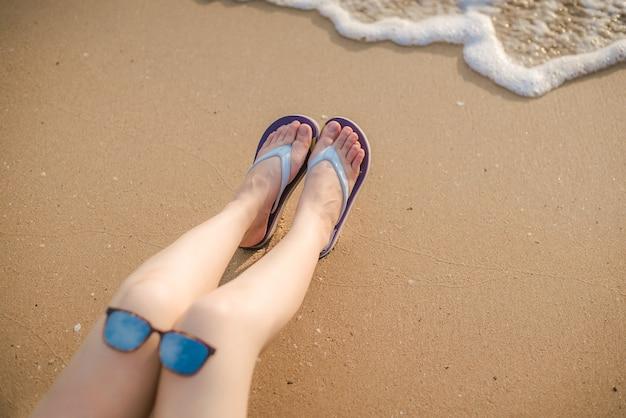 彼女のカンガに彼女の手と彼女の膝の上に花と眼鏡をかけて海のそばの岩の上に座っている女性