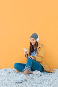 핸드폰을 사용 하여 헤드폰으로 양탄자 듣는 음악에 앉아있는 여자