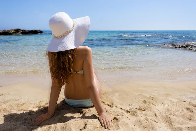 모래에 앉아서 푸른 바다를 찾는 여자