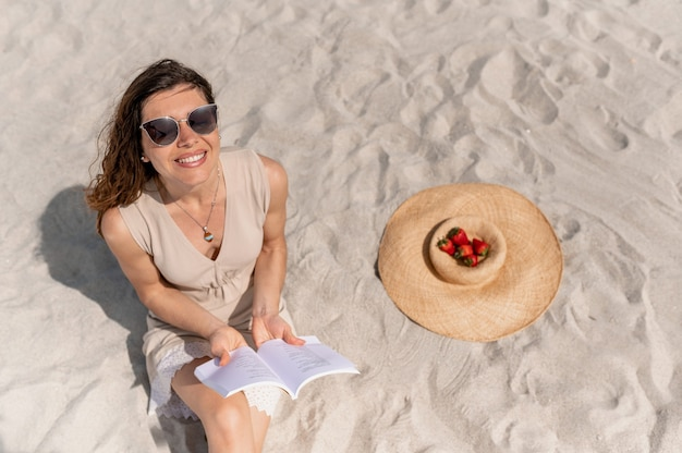 Женщина сидит на песке, читает книгу и смотрит вверх, смеясь, выстрел из соломенной шляпы с фруктами